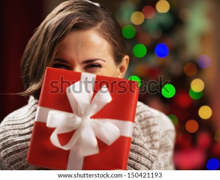 Happy young woman holding christmas present box in front of face - stock photo