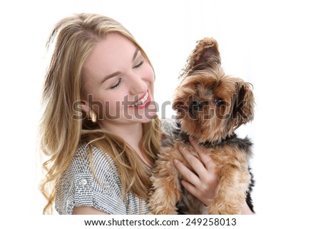 Happy young woman holding cute small dog - stock photo
