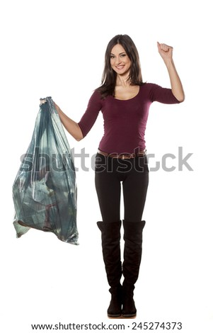 happy young woman holding garbage bag and showing winning gesture - stock photo