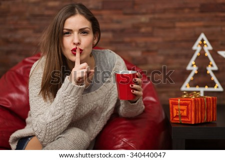 Happy young woman holding gift box at her home - stock photo