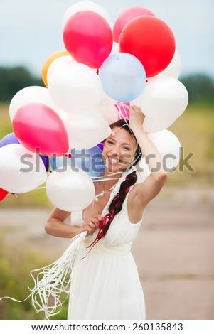Happy young woman holding in hands colorful latex balloons outdoors. Beautiful bride in white dress having fun in wedding day. Smiling and laughing woman. Carefree people. Decor for party celebration - stock photo
