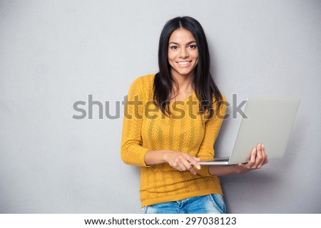 Happy young woman holding laptop and looking at camera over gray background - stock photo