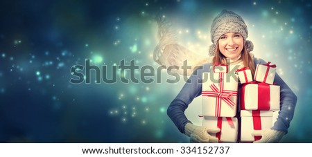 Happy young woman holding many present boxes in snowy night - stock photo