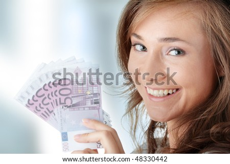 Happy young woman holding money - stock photo