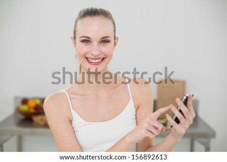 Happy young woman holding smartphone smiling at camera in the kitchen at home - stock photo