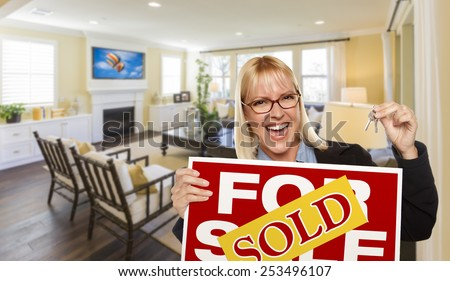 Happy Young Woman Holding Sold For Sale Real Estate Sign and Keys Inside Beautiful Custom Living Room. - stock photo