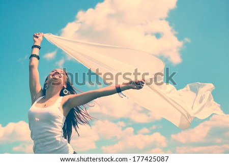 Happy young woman holding white scarf with opened arms expressing freedom, outdoor shot against blue sky, toned - stock photo