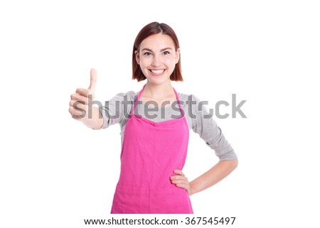 Happy young woman housewife mother wearing kitchen apron and showing thumbs up, caucasian - stock photo