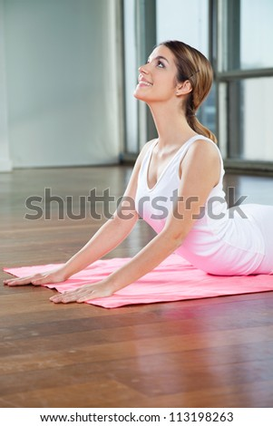 Happy young woman in a cobra pose on mat - stock photo