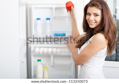 Happy young woman in a kitchen drinking a glass of fresh juice with a bowl of delicious fruit - stock photo