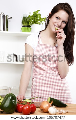 happy young woman in a kitchen nibbling on a cucumber while chopping for salad - stock photo