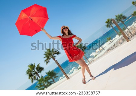 Happy young woman in a red dress with a red umbrella on seafront background - stock photo