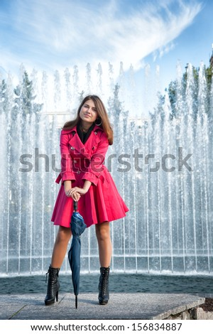 happy young woman in a red raincoat with an umbrella - stock photo