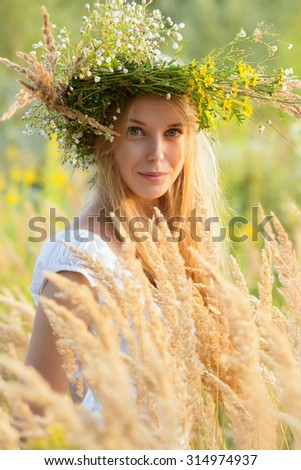 happy young woman in a wreath from a grass - stock photo