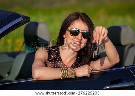 Happy young woman in convertible outdoor - stock photo