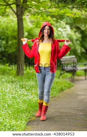 Happy young woman in hooded red raincoat holding red umbrella. She is looking at camera and smiling while walking in the park on a rainy day. - stock photo
