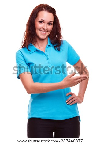 Happy young woman in polo shirt showing empty copyspace - stock photo