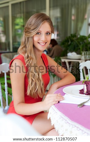 happy young woman in red dress resting in the cafe - stock photo