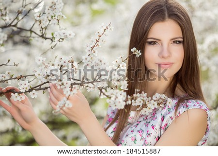 Happy young woman in spring flowers garden lifestyle portrait. beautiful teen girl in spring park enjoying nature. Spring concept. Series. - stock photo