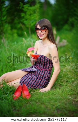 happy young woman in sunglasses sitting on the grass with a cocktail. - stock photo