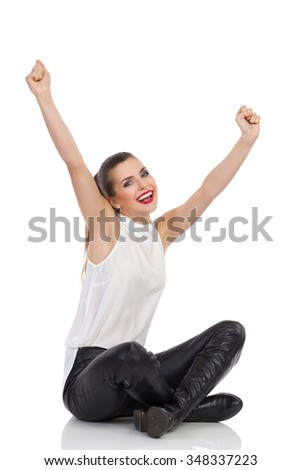 Happy young woman in white shirt, black leather trousers and boots sitting on a floor with legs crossed and rising arms. Full length studio shot isolated on white. - stock photo