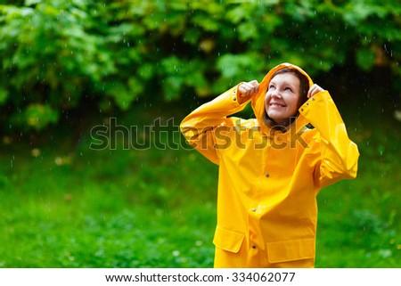 Happy young woman in yellow raincoat under rain - stock photo