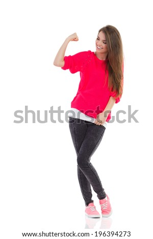 Happy young woman is flexing muscle. Full length studio shot isolated on white. - stock photo