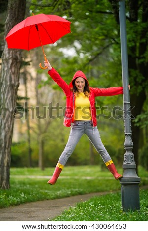 Happy young woman is having fun on the rain. She climbed the outdoor lamp post in the park, smiling and looking at camera. - stock photo