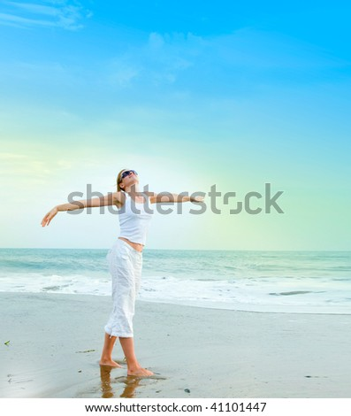 happy young woman is jumping in the beach - stock photo