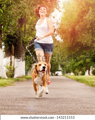 Happy young woman jogging with her beagle dog - stock photo