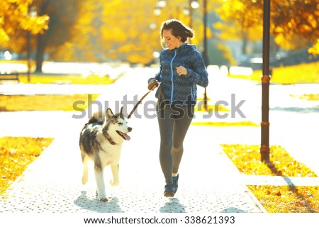 Happy young woman jogging with her dog in park - stock photo
