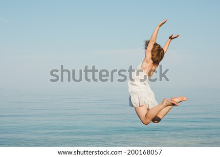 Happy young woman jumping on the beach  - stock photo