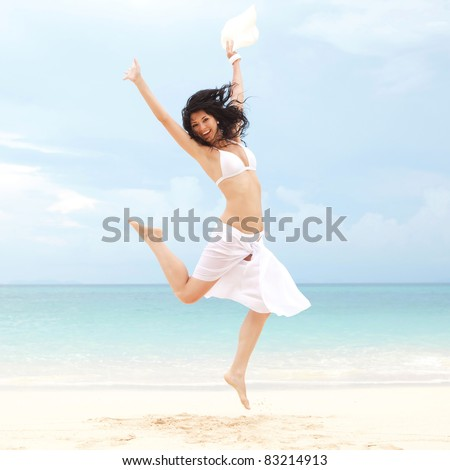 happy young woman jumping on the beach of sea - stock photo