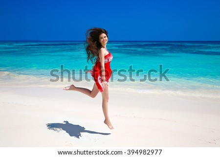 Happy young woman jumping on the sea, brunette smiling girl in red dress running on tropical beach with white sand. Enjoyment. Lifestyle. Freedom. Good life. Travel.  - stock photo