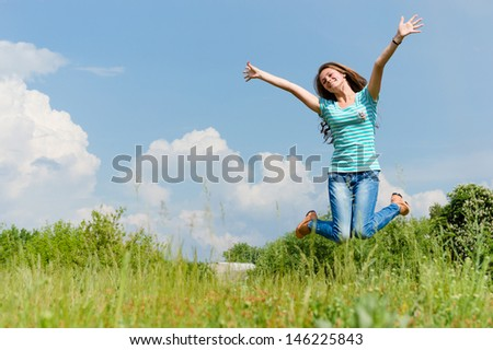happy young woman jumping on the summer outdoors background - stock photo
