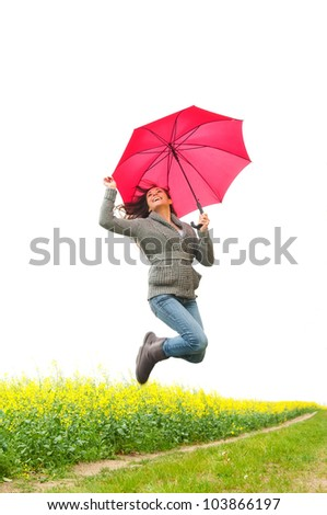 happy young woman jumping with umbrella - stock photo