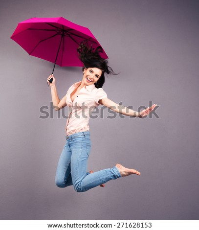 Happy young woman jumping with umbrella over gray background. Looking at camera - stock photo