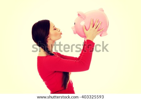 Happy young woman kissing a piggybank - stock photo
