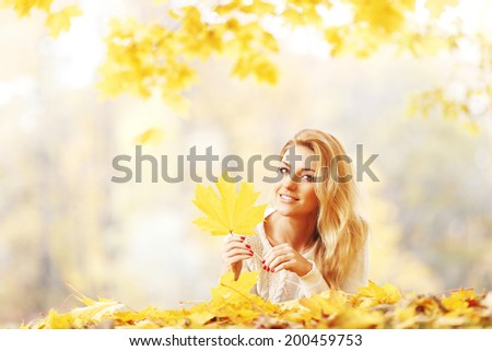 Happy young woman laying on autumn leaves in park - stock photo