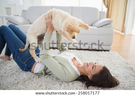 Happy young woman lifting puppy while lying on rug at home - stock photo