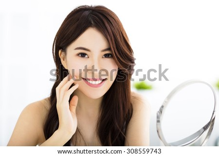 Happy young woman  looking on mirror - stock photo
