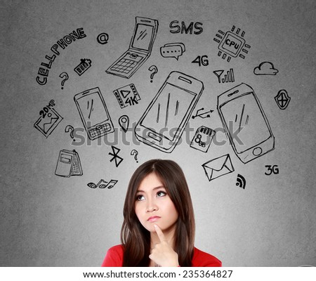 Happy young woman looking up, thinking what mobile phone to buy - stock photo