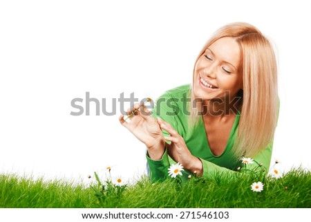 Happy young woman lying on grass with chamomile flowers, isolated on white background - stock photo