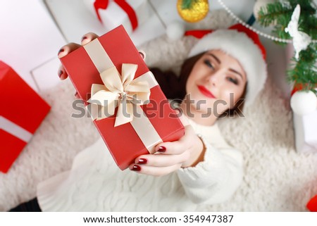 Happy young woman lying on the floor with gift box  - stock photo