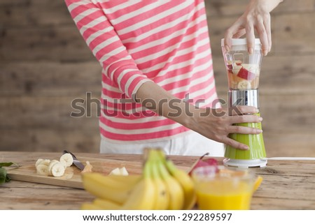 Happy young woman making healthy fruit smoothies in her kitchen peeking around the liquidizer and fresh fruit ingredients with a friendly smile - stock photo