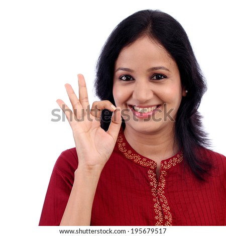 Happy young woman making OK sign against white background - stock photo