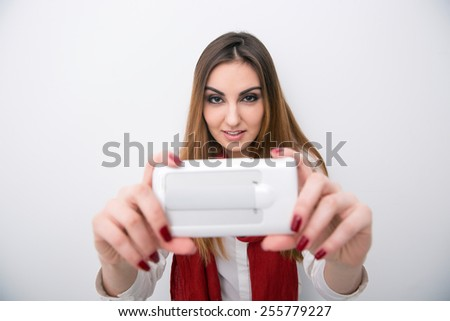 Happy young woman making photo on smartphone over gray background - stock photo