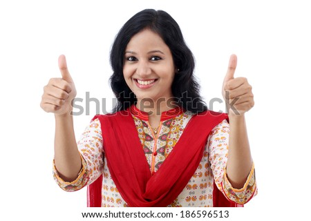 Happy young woman making thumbs up sign against white - stock photo