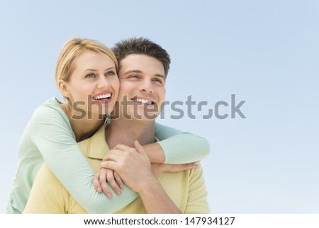 Happy young woman man from behind while looking away against clear blue sky - stock photo