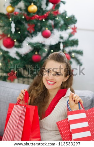 Happy young woman near Christmas tree with shopping bags - stock photo